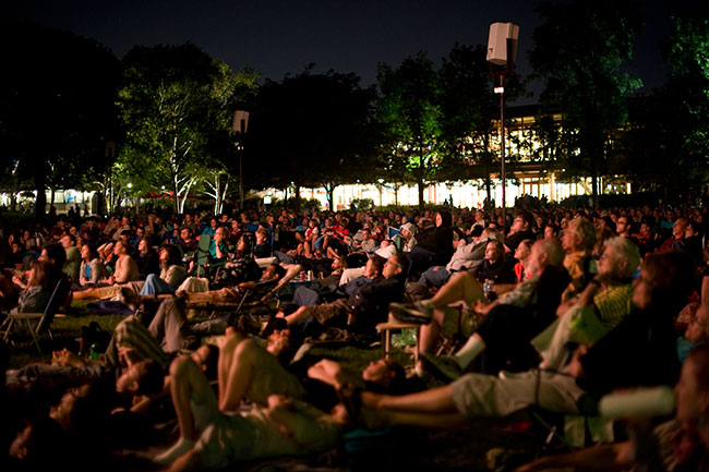 Ravinia patrons sitting and laying on the ground at night with a building lit up in the background
