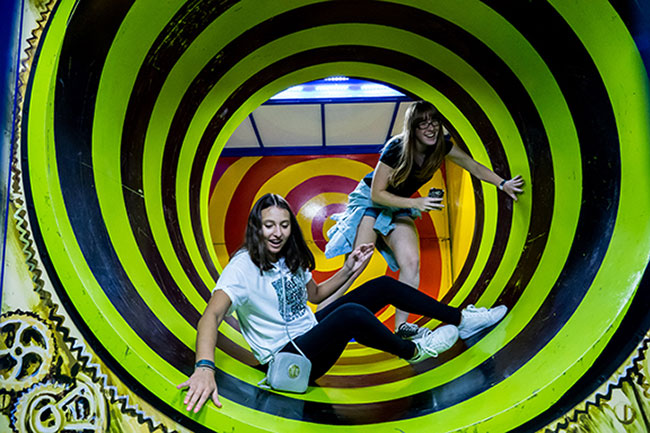 two girls in a green and black funhouse spinning tube