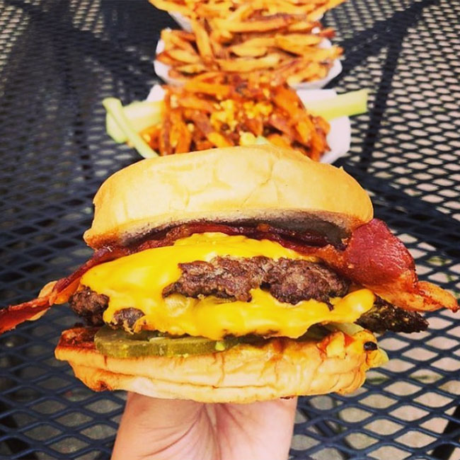 Edzo's Burger Shop, Evanston, cheeseburger in a hand with fries behind it