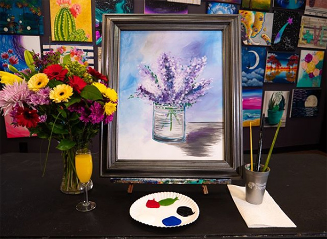 real flowers in vase to left of canvas with painted purple flowers, Pinot's Palette, Glenview