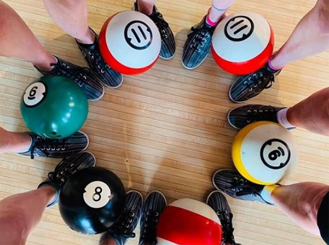 Circle of feet in bowling shoes with colorful bowling balls, Pinstripes, Northbrook